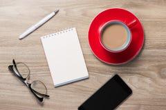 Öppen tom vit anteckningsbok, monokel, penna och kopp kaffe på skrivbordet royaltyfri fotografi