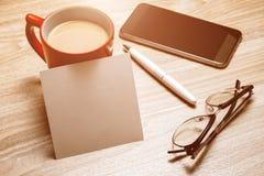 Öppen tom vit anteckningsbok, monokel, penna och kopp kaffe på skrivbordet arkivfoton