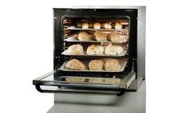 Öppen ugn med nytt bakat bröd på vit bakgrund Royaltyfri Bild