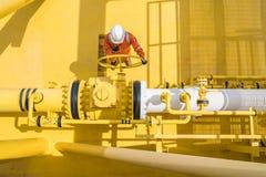 Öppen ventil för produktionoperatör som låter gas som flödar till havslinjen rör för överförd gaser och råolja till den centrala  arkivbild