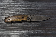 Öppen vikt kniv på svart Wood bakgrund Arkivfoto