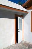 Öppen vit dörr med apelsinklippning Arkivfoto