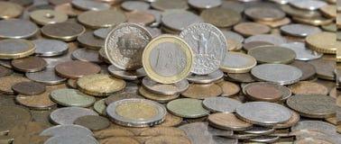 Öppenhjärtig, euro och dollar på bakgrund av många gamla mynt royaltyfri bild