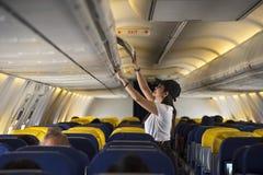 Öppet över huvudet skåp för handelsresandekvinna på flygplanet royaltyfria bilder