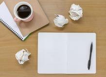 Öppet anteckningsböcker, papper och kaffe på ett träskrivbord r fotografering för bildbyråer