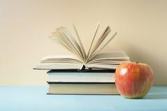 Öppet bok, inbunden bokböcker och äpple på trätabellen sax och blyertspennor på bakgrunden av kraft papper tillbaka skola till Ko Royaltyfri Bild