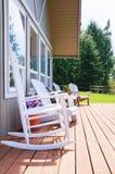 Öppet främre däck för lantgårdhus med vita stolar. Arkivfoton