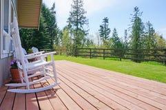 Öppet främre däck för lantgårdhus med vita stolar Fotografering för Bildbyråer