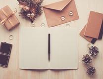 Öppet notepad för vit, kuvert och julgarnering som ligger på beige träbakgrund, lekmanna- lägenhet, copyspace, tonad bild arkivfoto