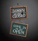 Öppet och stängt tecken på svart tavla som hänger med kedjan Arkivfoton