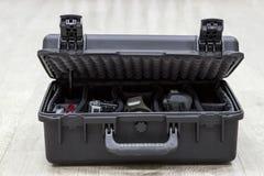 Öppet plast- fall för bit på golv med fotoutrustning i avdelare Fotografering för Bildbyråer