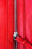 Öppet slut för blixtlås delvis upp detaljmakrofotoet på en röd lädertexturbakgrund i vertikalt format arkivbilder