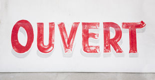 Öppet tecken för gammal sliten Ouvert fransman Arkivbild