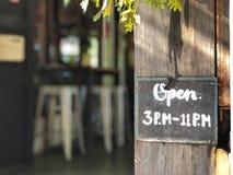 Öppet tecken, meddelande om tid för Open 3 e.m. till 11 e.m. som är skriftliga i krita Royaltyfri Bild