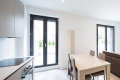 Öppet utrymme med elegant kök och vardagsrum fotografering för bildbyråer