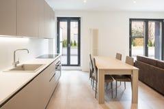 Öppet utrymme med elegant kök och vardagsrum royaltyfri bild