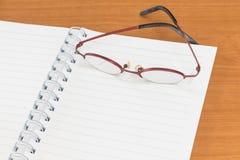 Öppna anmärkningsboken med exponeringsglas Arkivfoto