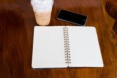 Öppna anmärkningsboken med kaffekoppen och smartphonen Fotografering för Bildbyråer