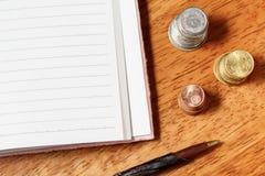 Öppna anteckningsbok, blyertspenna och buntar för mellanrum av mynt Arkivfoto