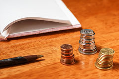 Öppna anteckningsbok, blyertspenna och buntar för mellanrum av mynt Royaltyfria Bilder