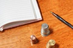 Öppna anteckningsbok, blyertspenna och buntar för mellanrum av mynt Arkivbilder