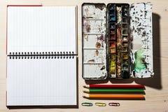 Öppna anteckningsbok-, blyertspenna- och vattenfärgmålarfärger Royaltyfri Fotografi