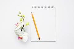 Öppna anteckningsboken med blyertspennan och blommar orkidén Royaltyfri Fotografi