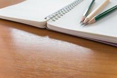 Öppna anteckningsboken med blyertspennor Arkivfoton