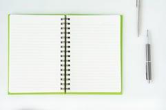 Öppna anteckningsboken med den metalliska bollpennan Royaltyfri Fotografi