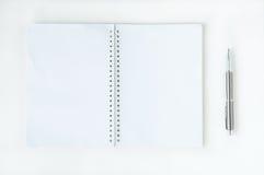 Öppna anteckningsboken med den metalliska bollpennan Arkivfoto