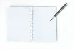 Öppna anteckningsboken med den metalliska bollpennan Royaltyfri Bild
