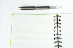 Öppna anteckningsboken med den metalliska bollpennan Royaltyfri Foto