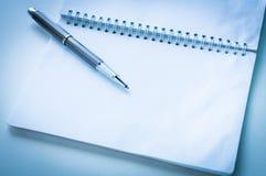 Öppna anteckningsboken med den metalliska bollpennan Royaltyfria Foton