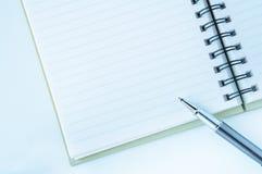 Öppna anteckningsboken med den metalliska bollpennan Royaltyfria Bilder