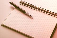 Öppna anteckningsboken med den metalliska bollpennan Arkivbild