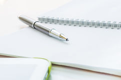 Öppna anteckningsboken med den metalliska bollpennan och minnestavlan Arkivfoton