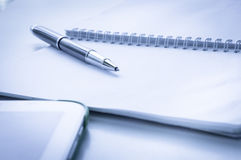 Öppna anteckningsboken med den metalliska bollpennan och minnestavlan Arkivbild
