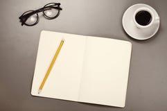 Öppna anteckningsboken med en blyertspenna, exponeringsglas och kaffekoppen Arkivfoto