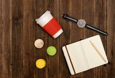 Öppna anteckningsboken med en blyertspenna, makron, papper-koppar och klockor på en träbakgrund Royaltyfria Bilder