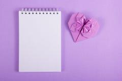 Öppna anteckningsboken med en tom sida och en origamihjärta VALENTINPAPPER Pappers- hjärta för lila Royaltyfri Fotografi