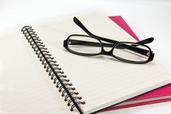 Öppna anteckningsboken med exponeringsglas på en rosa anteckningsbok Fotografering för Bildbyråer