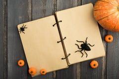 Öppna anteckningsboken med halloween garnering på trätabellen Royaltyfri Foto