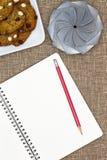 Öppna anteckningsboken med mutterkakor och en gåva Arkivbilder