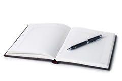 Öppna anteckningsboken med pennan arkivbild