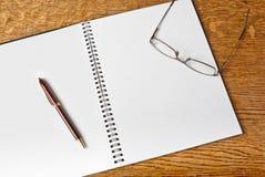 Öppna anteckningsboken med skrivar och exponeringsglas Royaltyfria Foton