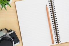 Öppna anteckningsboken med tappningkameran på wood bakgrund Royaltyfri Foto