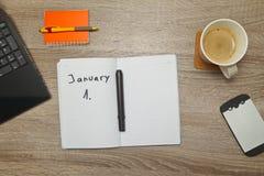 Öppna anteckningsboken med text`-JANUARI 1st ` och en kopp kaffe på träbakgrund Royaltyfri Bild