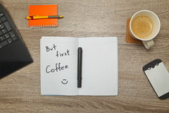 Öppna anteckningsboken med text` MEN FÖRSTA KAFFE` och en kopp kaffe på träbakgrund Arkivfoto