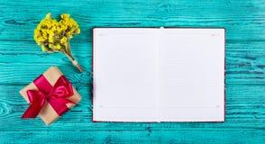 Öppna anteckningsboken med tomma sidor, gåvaasken med bandet och blommor royaltyfri fotografi