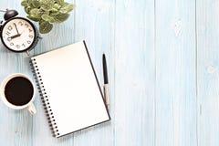Öppna anteckningsboken med tomma sidor, kaffekoppen och klockan på träskrivbordtabellen Fotografering för Bildbyråer